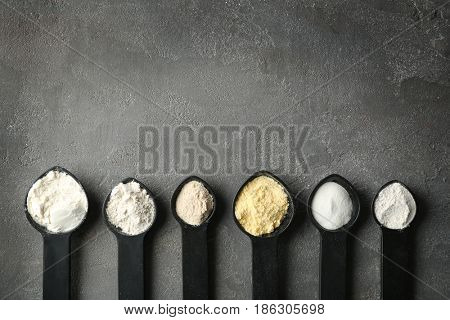 Spoons with different types of flour on grey textured background