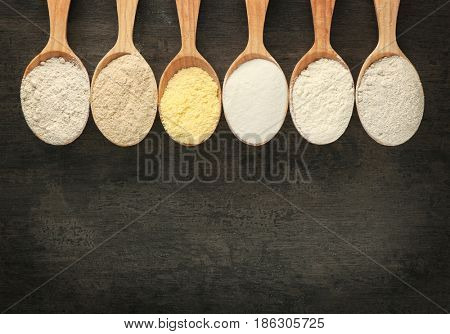Spoons with different types of flour on dark wooden background