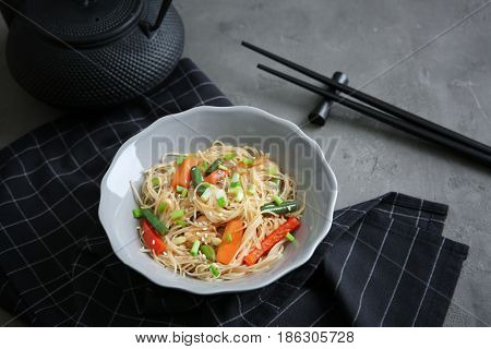 Delicious rice noodle with vegetables on grey table