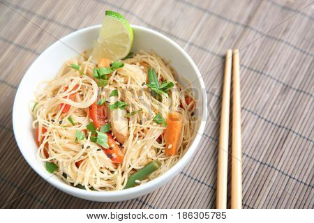 White plate with tasty rice noodle and vegetables on table