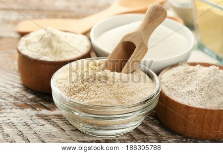 Bowls with different types of flour on wooden table, closeup