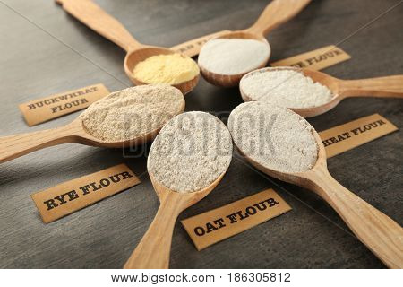 Spoons with different types of flour on grey wooden background