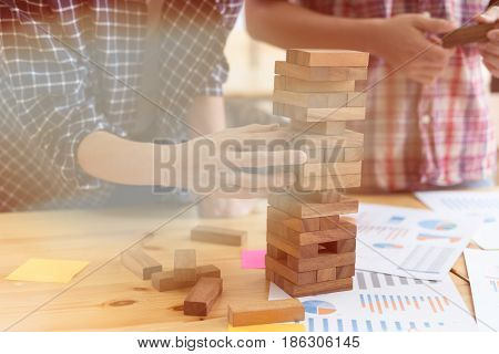 Young Start Up People Take One Block From Wooden Blocks Tower With Marketing And Financial Graph And