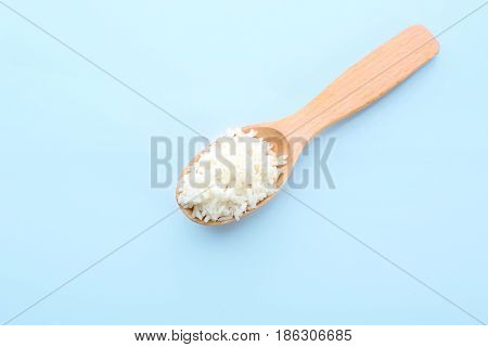 Wooden spoon with coconut rice on blue background