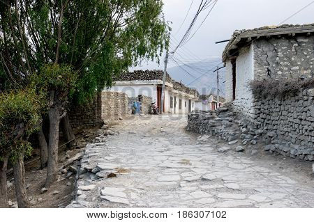 A flagstone road going through a small town with stone houses in Jomsom Nepal.