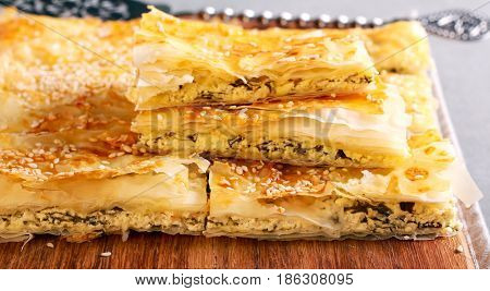 Spanakopita or spinach pie - a Greek savory pastry on board