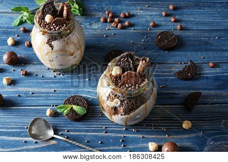 Delicious parfait with chocolate in jar on wooden background
