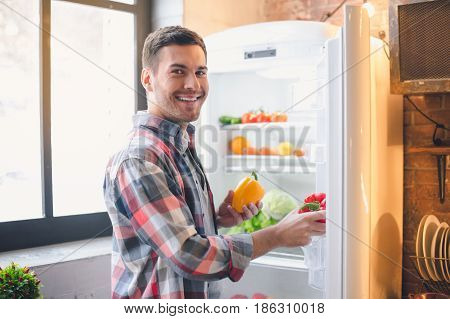 Young man vegan put purchases healthy products in refrigerator