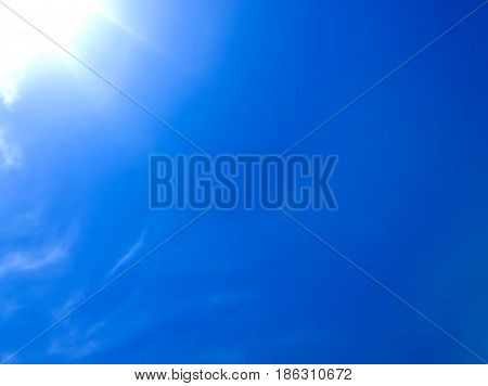 Part of a bright dazzling sun in an empty blue sky