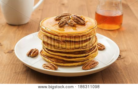 Vegan butternut squash puree pancakes on white plate with maple syrup and pecan nuts. Healthy gluten free breakfast on wooden table