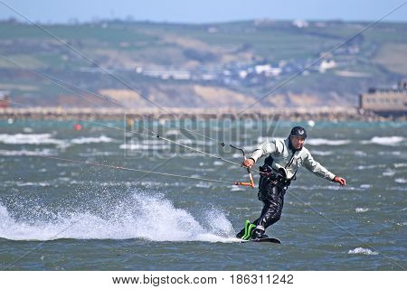 kitesurfer riding toeside on his kite board