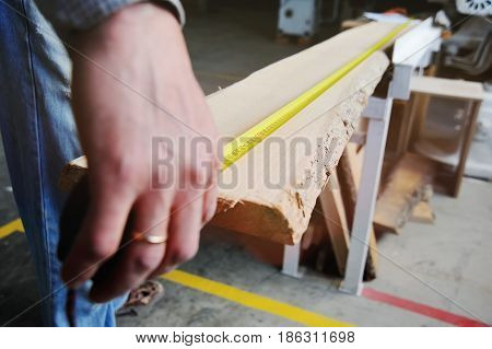 Carpenter makes the marking of the board with a measuring tape measure on the background of the joiner's workshop