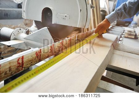 The joiner makes the marking of the board with a measuring tape measure on the background of the joiner's workshop