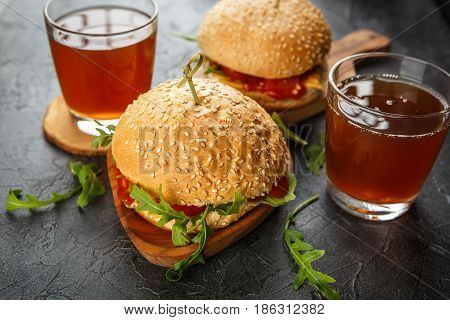 Two homemade hamburgers with arugula, tomato and cheese and drinks on a dark background