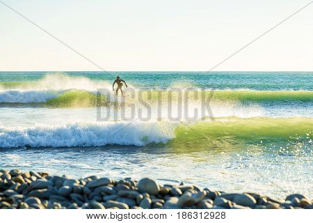 Clear waves and surfer on wave. Surfing in green waves.