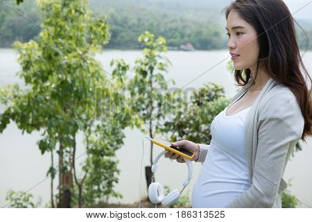 Young Asian Woman Standing In Fresh Spring Garden Holding Mobile Phone And Headphone Smiling With Pl
