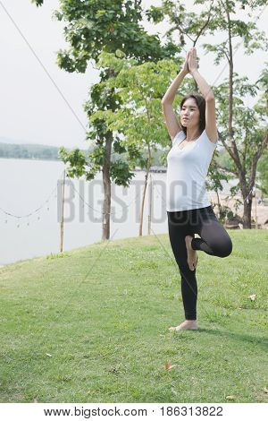 Asian Pregnant Woman Practicing Yoga On Green Grass In Public Park.  Concept Of Prenatal Exercise, M