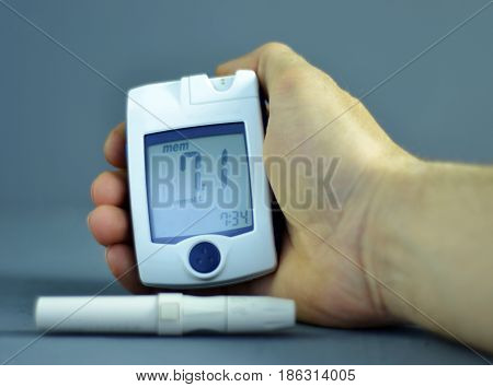 Human hand, Glucometer on a dark background of sugar in the blood. The concept of diabetes