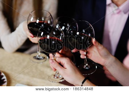 Friends celebrate a festive event in a restaurant and clink glasses with wine