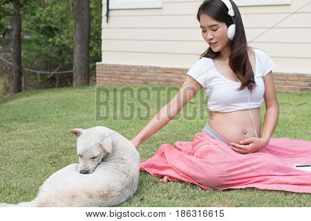 Young Asian Woman Sitting In Fresh Spring Grass Listening To Music And Playing With White Dog. Beaut