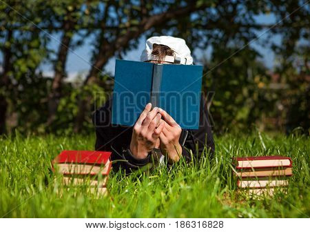 Person with a Books on the Summer Meadow