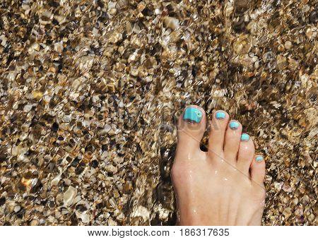 Female leg with beautiful menthol pedicure on the seashore