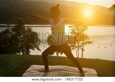 Silhouette Of Asian Pregnant Woman Practicing Yoga On Green Grass In Public Park.  Concept Of Prenat