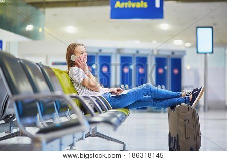 Young Travelerin International Airport Checking Her Mobile Phone While Waiting For Her Flight
