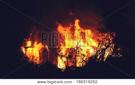 Arson or nature disaster - burning fire flame on wooden house roof. Big fire at night