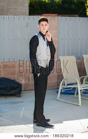 Handsome Mexican teen holding jacket over shoulder in formal black suit.