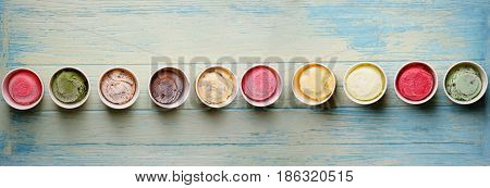 Row of assorted flavors and colors of gourmet Italian ice cream on wood table panorama