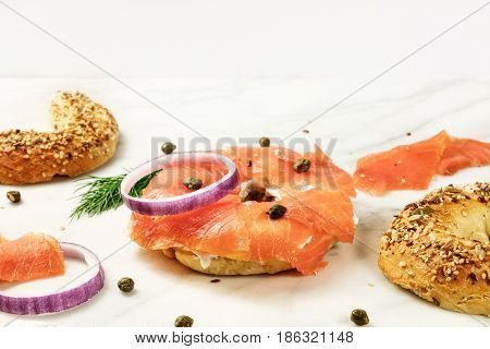 Bagel ingredients. Lox, purple onions, capers, dill, and the buns, shot on a white marble background in the process of making, with a place for text