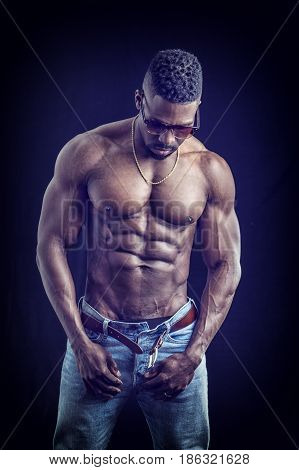 African American bodybuilder man, naked muscular torso, wearing jeans and sunglasses, on black background