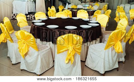 Chairs With Yellow Cloth And Table For Guests Served With Empty Plates And Covered With Brown Tablec