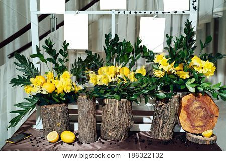 Wedding Flower Arrangements Of Yellow Daffodils, Greenery And Lemons On Stumps Under Seating Plan Fo