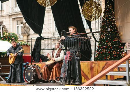 Prague, Czech Republic, December 13, 2016: Christmas performance on stage in Prague's main square. The ethnic collective plays on bagpipes and other national instruments.