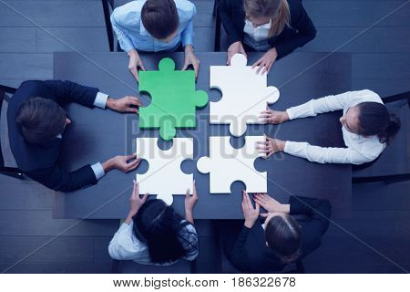 Business People Assembling Puzzle