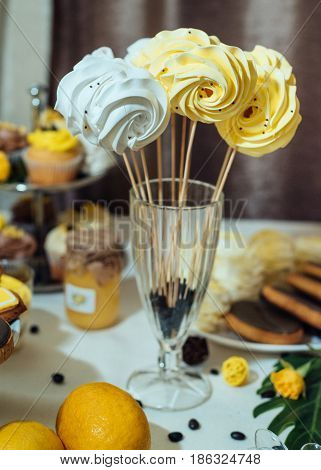 White And Yellow Meringues On Stick In Glass With Coffee Beans. Holiday Candy Bar In Yellow And Brow