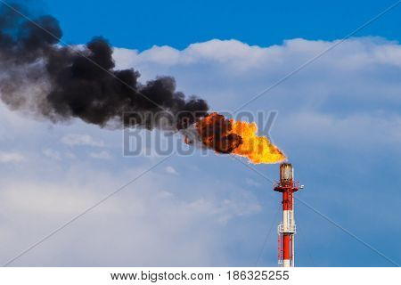 Refinery chimney with fire, black smoke and fire with blue sky background