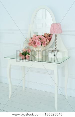 White Boudoir Table With Oval Mirror, Pink Flowers And Lamp On It In White Room. Detail Of The Inter