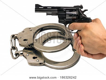 Gun in hand against the background of police handcuffs. Adventure and justice.