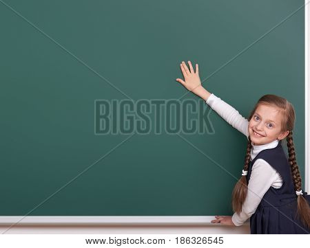 elementary school girl put hands on chalkboard background and show blank space, dressed in classic black suit, group pupil, education concept