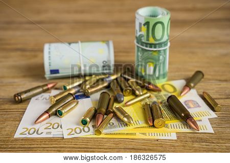 Banknotes and bullets, money on the wooden table