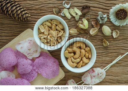 Roasted cashew nuts and peanuts with magenta crisp rice crackers appetizer in white bowl on wooden table.