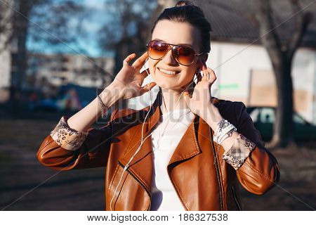 Smiling pretty brunette in sunglasses and red leather jacket listening music with closed eyes. Fashionable positive woman walking at park in sunny day enjoying and relaxing.