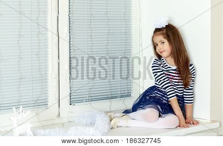 Little girl in blue striped dress and a white bow on her head.She sits at the window turned away from the camera.