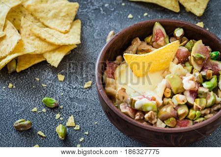 Baked Soft Cheese Brie With Figs, Walnuts, Pistachios And Honey In A Bowl. Snack Concept With Chips.