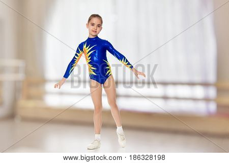 Beautiful Russian girl gymnast younger school age, in blue in a sports swimsuit.The girl performs a difficult acrobatic exercise.In the sports hall with mirror and a large semi-circular window.