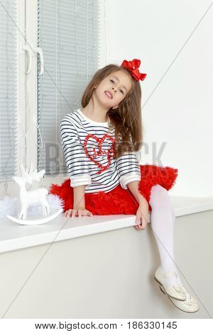 Beautiful little girl a bright red bow on head and red skirt sitting by the window.She put one leg over the other.