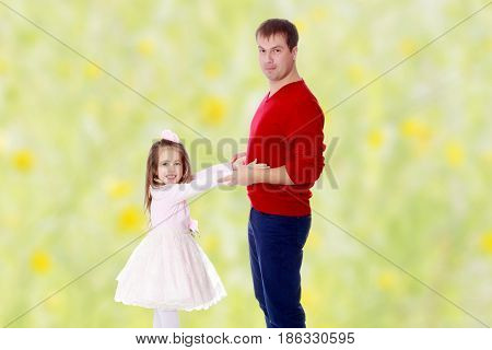 Cute little long-haired girl in a smart pink dress , reaches out to his dad.Summer white green blurred background.